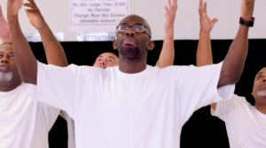 The actors are standing up with white t-shirts. Their hands are raised upwards and they are looking up.